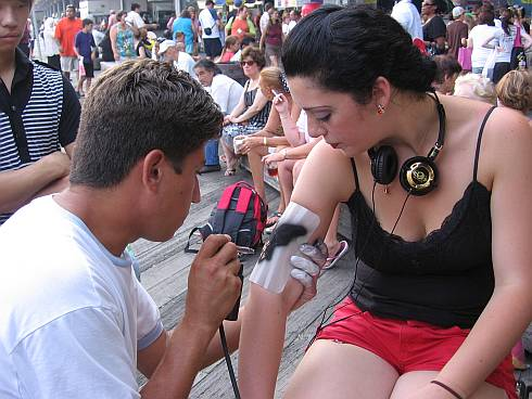 A girl getting an air-brush tattoo