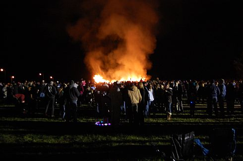 a burning boat, crowd watching