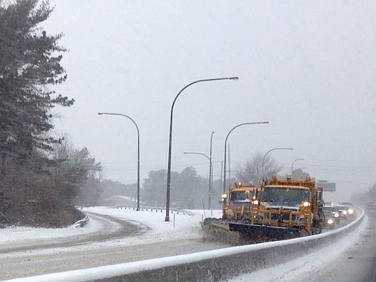 Snow plows with traffic behind them